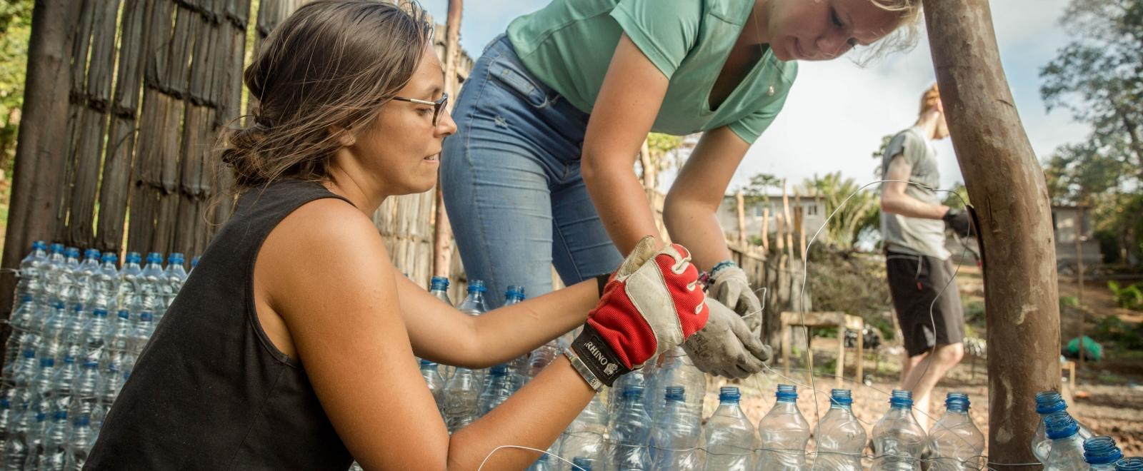Projects Abroad Conservation volunteers build an eco-wall using recycled plastic in the Galapagos Islands, Ecuador.